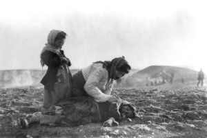 An Armenian woman kneeling beside a dead child in a field within sight of help and safety at Aleppo circa 1915