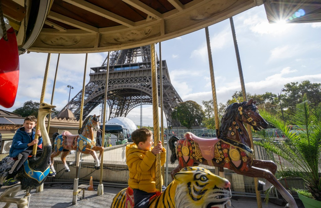 Carousel ride near Eiffel Tower Paris with kids