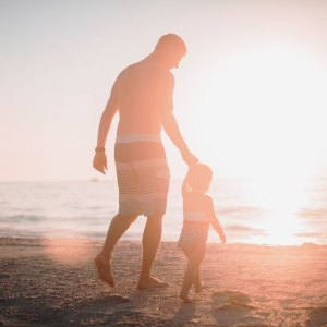 A father holding the hand of his daughter on the beach