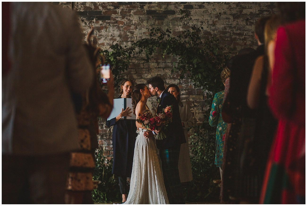 first kiss under floral archway