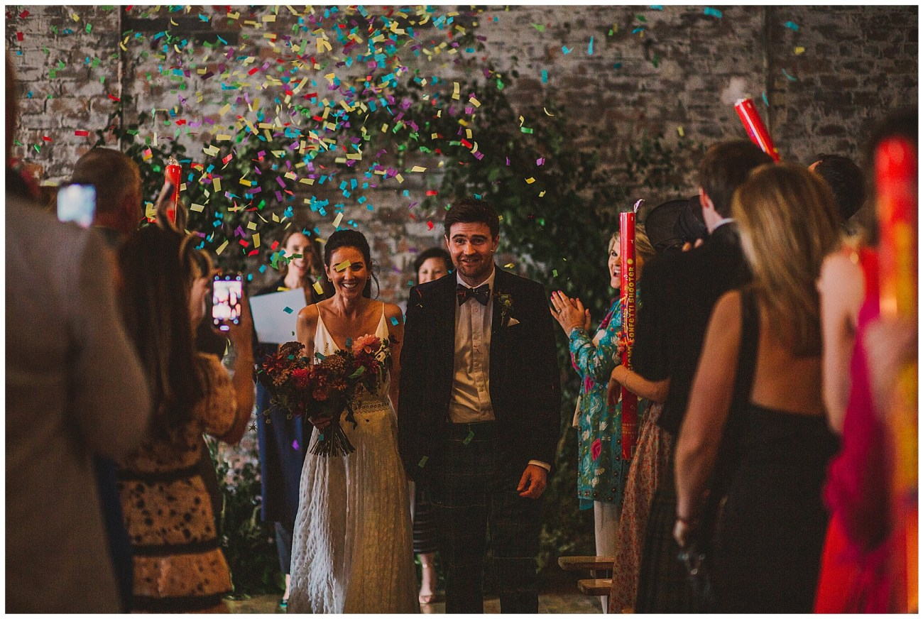 bride and groom walking with confetti canons