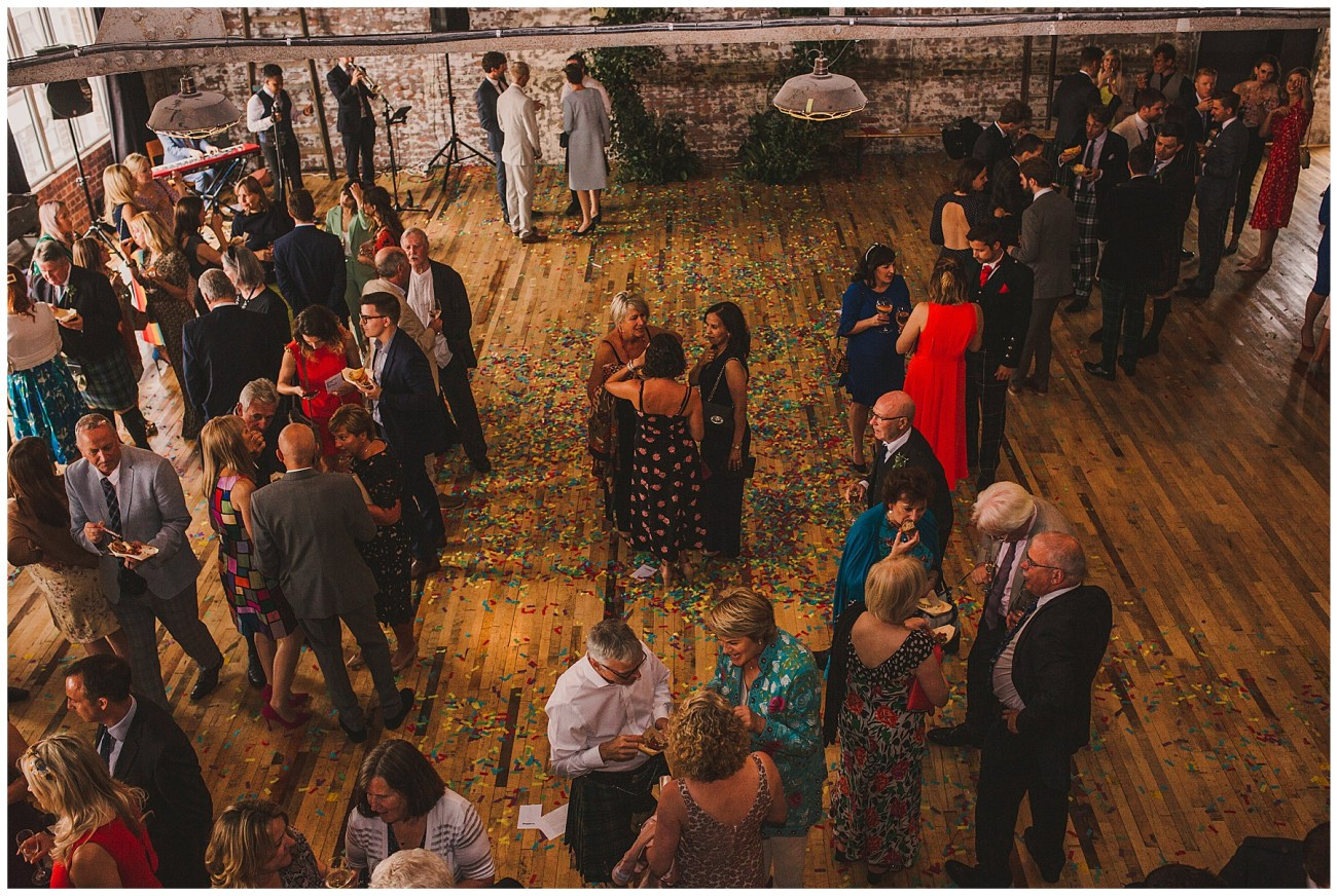 wedding ceremony room with guests mingling and confetti on the floor