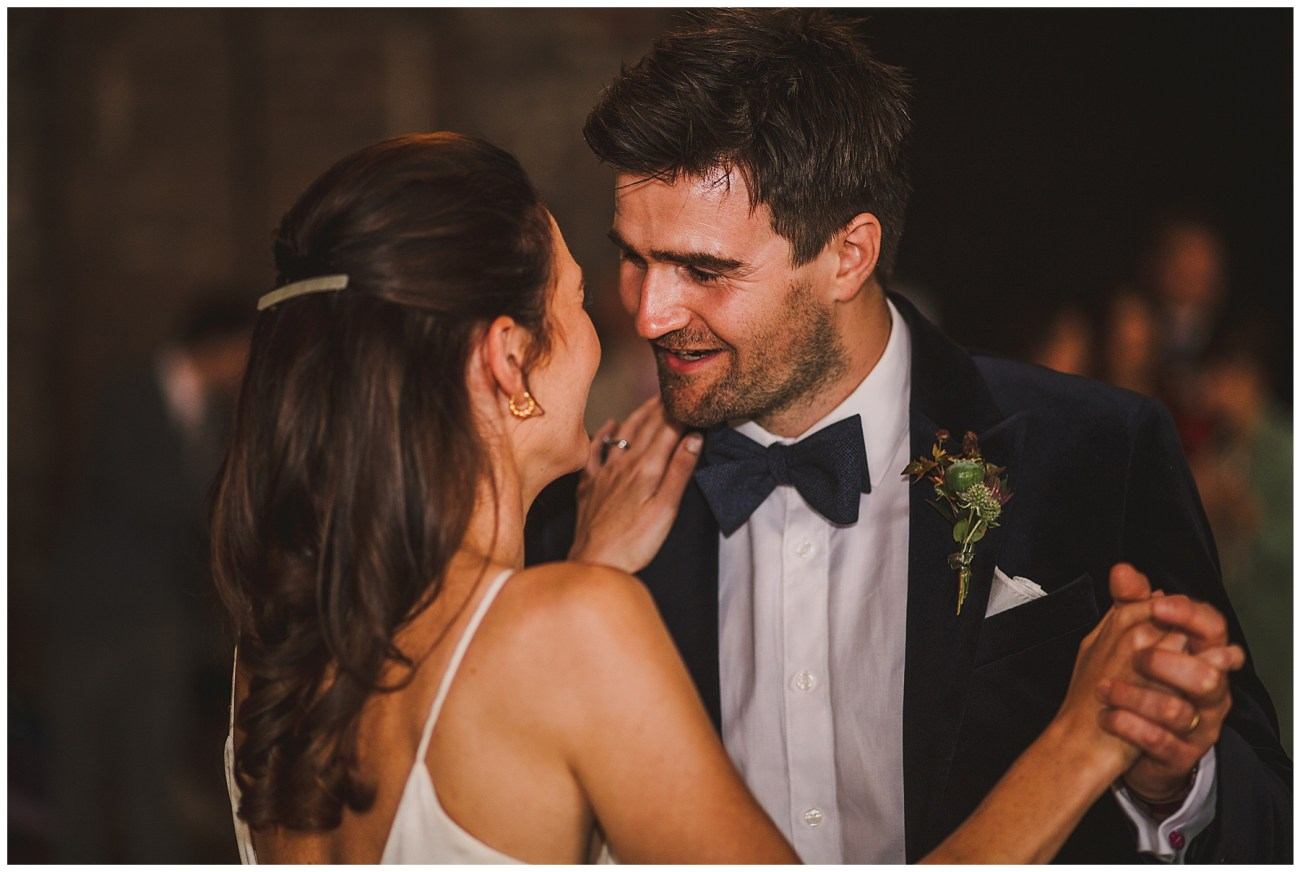 groom smiling whilst dancing with bride
