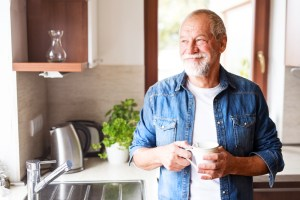 older man holding coffee cup