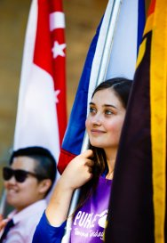 International students hold the flags of their home countries.
