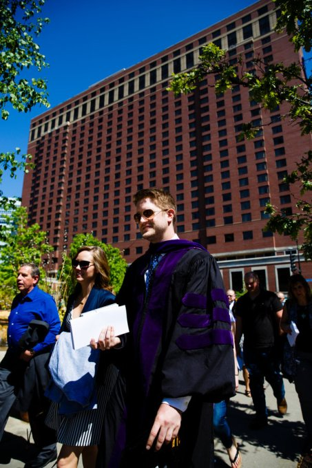 A new School of Law graduate (right) walks away from the Minneapolis Hilton following the School of Law Commencement ceremony May 13, 2017.