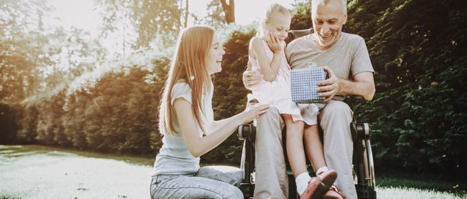 older-man-wheelchair-with-two-granddaughters