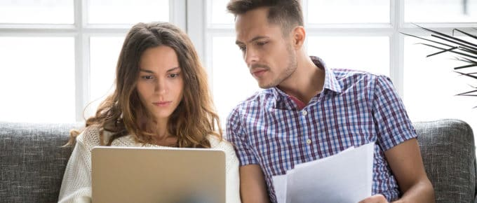couple-looking-at-laptop-while-doing-bills