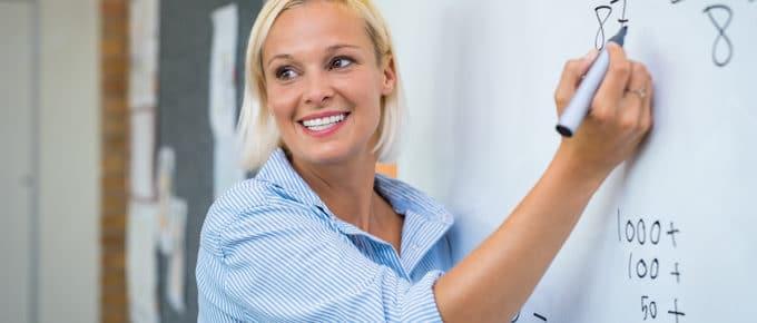 female-teacher-writes-whiteboard