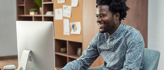 young-man-smiling-working-imac-computer