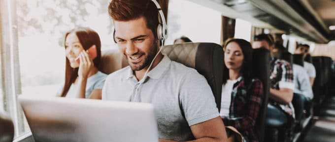 young-man-smiling-laptop-headphones-tour-bus
