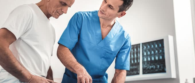 male-chiropractor-helping-male-patient