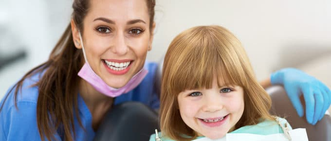 female-dental-hygienist-smiling-child-patient