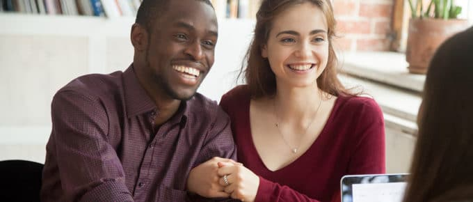 interracial-couple-smiling-buying-home