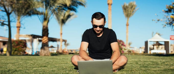 man-working-laptop-lawn-palm-trees