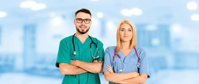 two-doctors-male-female-side-by-side-blue-hospital-background