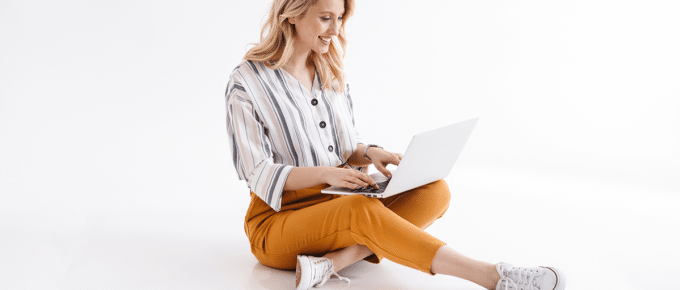 woman-smiling-laptop-sitting-white-studio-background
