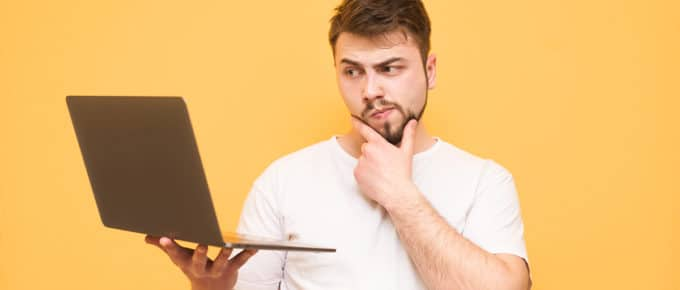 young-man-considering-laptop-golden-background