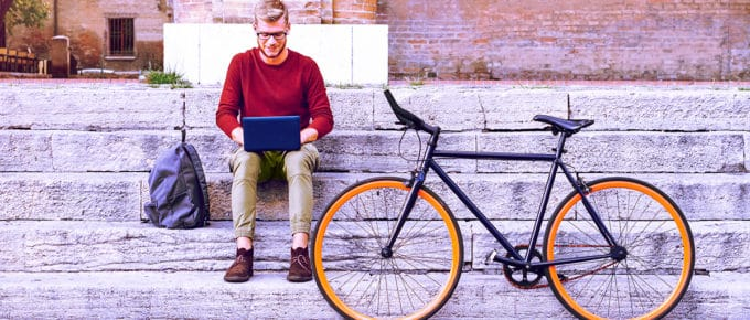 man-sitting-on-steps-outside-laptop-with-bicycle