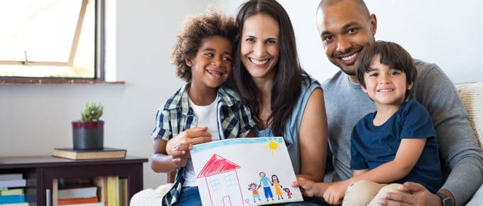 family-parents-two-children-smiling-showing-child's-drawing