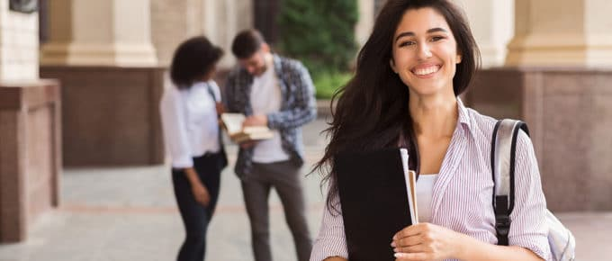 smiling-female-college-student-foreground-two-other-students-background