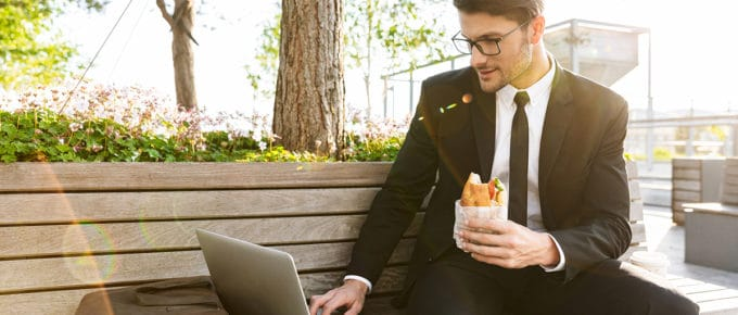 businessman-working-park-bench-laptop-holding-sandwich