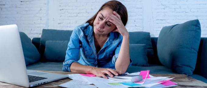 highly-stressed-woman-bills-cradling-head-hands