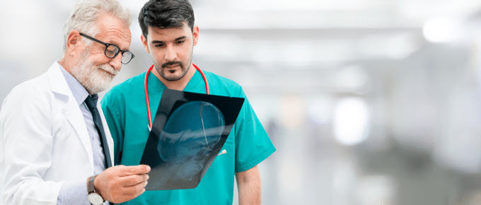 older-male-doctor-with-younger-male-doctor-examining-patient-xray
