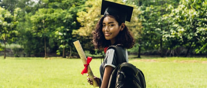 young-woman-holding-college-graduation-robes-diploma