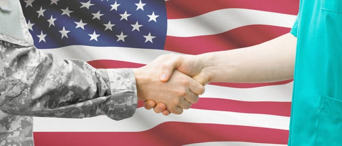 doctor-service-member-shaking-hands-american-flag-background