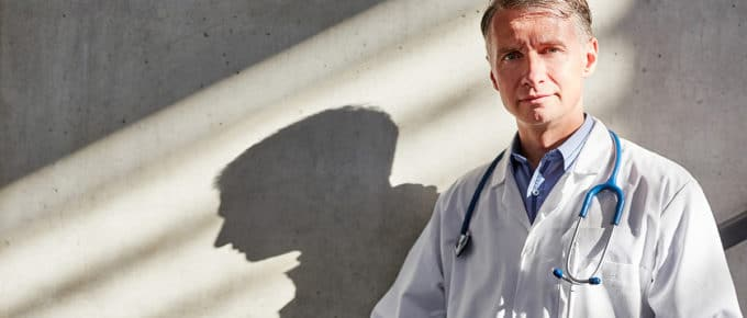 senior-doctor-outside-concrete-wall