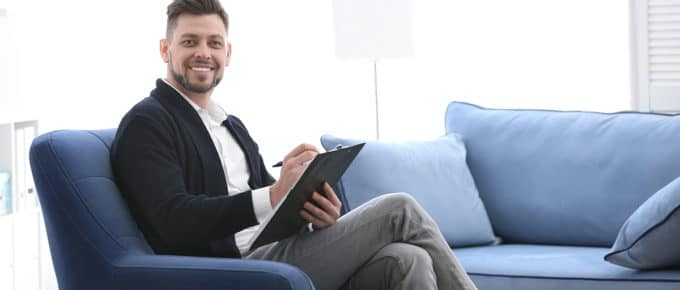 male-psychologist-clipboard-welcoming-couch-office