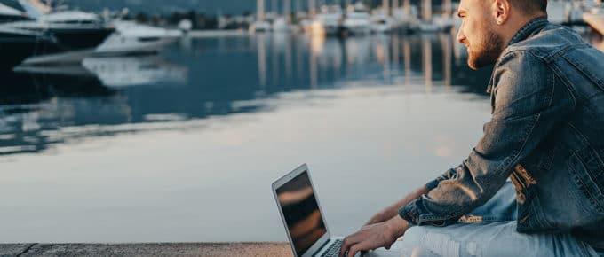 man-using-laptop-near-sea-harbor
