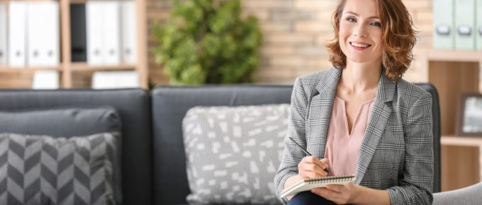 Attractive female psychologist sitting in armchair at office