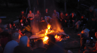 Camp fire surrounded by people