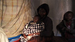 Mother with baby at home in Southlands Slum, Nairobi.