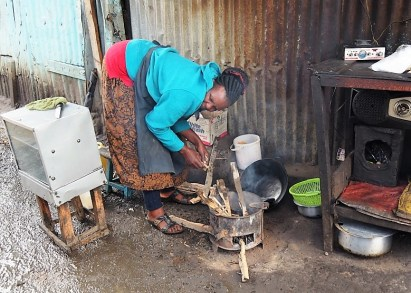 Woman making fire to sell cooked food.