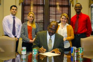 """President Rodney D. Bennett signs a proclamation designating Nov. 18-23 as """"Let's SAAC Hunger"""" week on the USM campus. Courtesy photo"""
