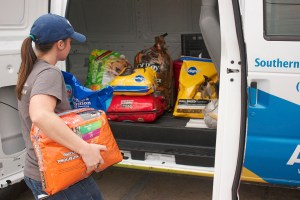 Brittany McAlister loads the Southern Pines Spay and Neuter Clinic van with pet food for the pet food bank. Hunt Mercier/Printz