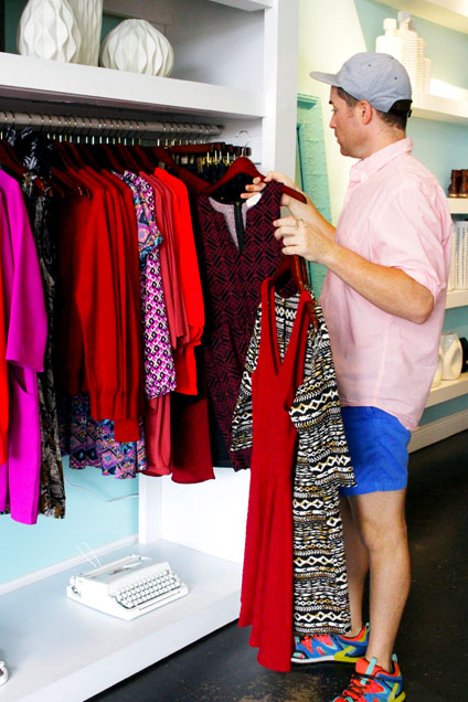 One of Click Boutique's owners, Adam Myrick, hangs new fall pieces. Click will be closing its doors this October and Myrick will open a new ladies Boutiue, Weekender, in Midtown this November. - Abby Smith