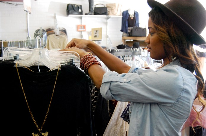 Arielle Waters, manager of United Apparel Liquidators, looks through the new stock of designer labels the store is carrying.  UAL has a wide assortment of game day apparel.- Mary Sergeant