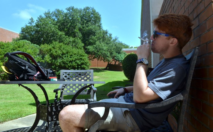 Senior Jay Spear stops to enjoy a cigarette after walking through Southern Miss campus on Sunday.  He sits in the shade in one of the designated smoking areas outside Joseph Greene Hall. - Aaron J. Stewart