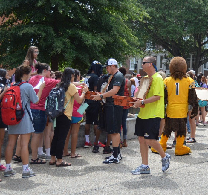 Head Southern Miss Football coach hands out pizza to the students  standing in line to receive their tickets to the Southern Miss vs. Mississippi State game, September 5th, 2015. Some students stood over an hour to receive their tickets to this game.