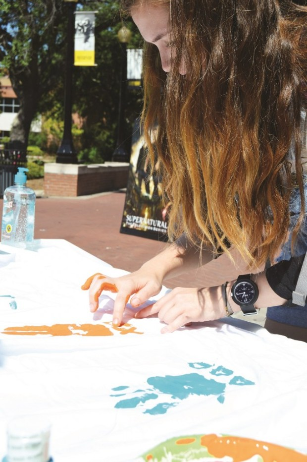 """Junior, Biological Science major, Chloe Webb signs her sorority letters on the """"These Hands Don't Haze"""" sheet that was made for National Hazing Prevention Week Sept 21- Sept 25th 2015. Jillian Rodriguez / Student Printz"""