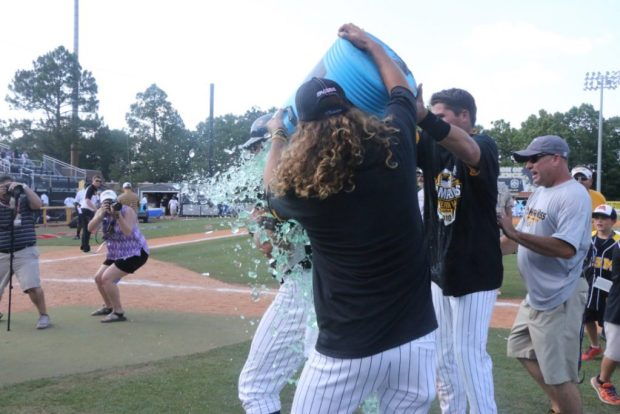Cord Cockrell and Tim Lynch douse Scott Berry after the Golden Eagles' 3-2 victory over Rice on May 29 in Pete Taylor Park.