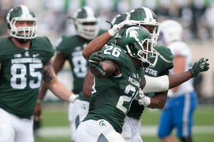 Senior safety RJ Williamson, 26, celebrates his interception with senior cornerback Arjen Colquhoun, behind, in the fourth quarter during the game against Air Force on Sept. 19, 2015 at Spartan Stadium. The Spartans defeated the Falcons, 35-21. Kennedy Thatch/The State News