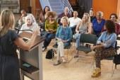 group-attending-neighborhood-meeting-listening-to-speaker-in-community-center