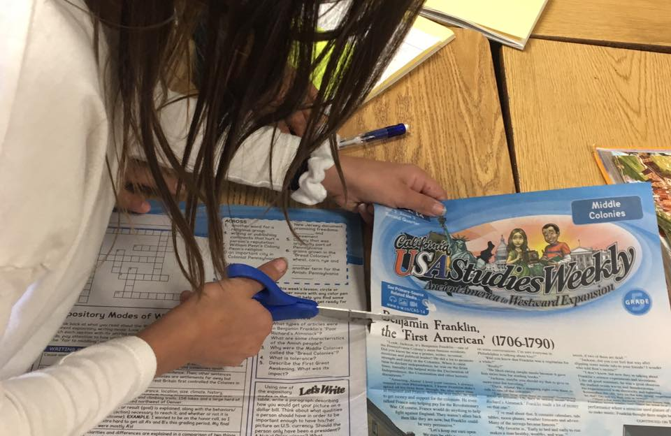 Student using studies weekly print material