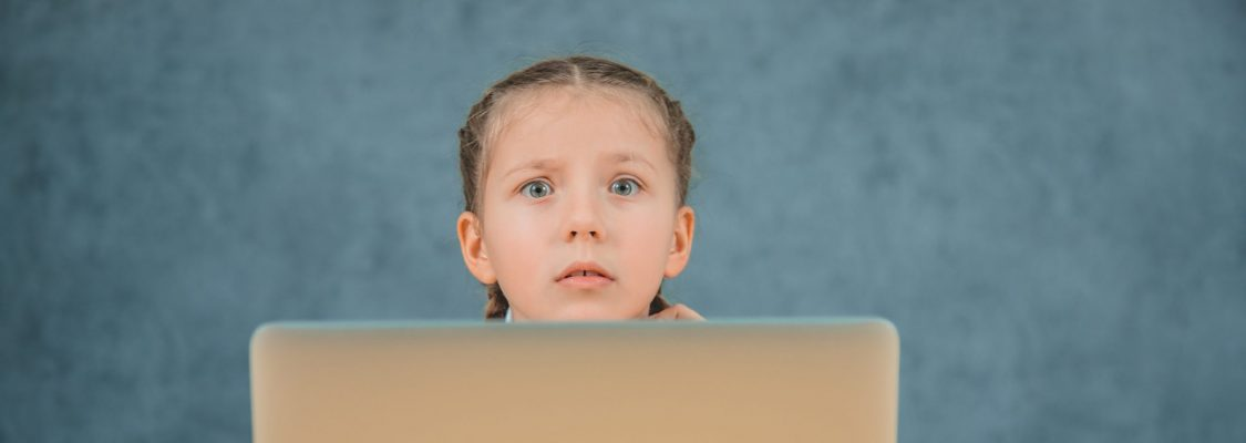 Confused schoolgirl with braids sitting in front of grey laptop isolated on grey background.