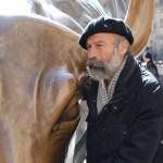 Arturo Di Modica posant près de son taureau.